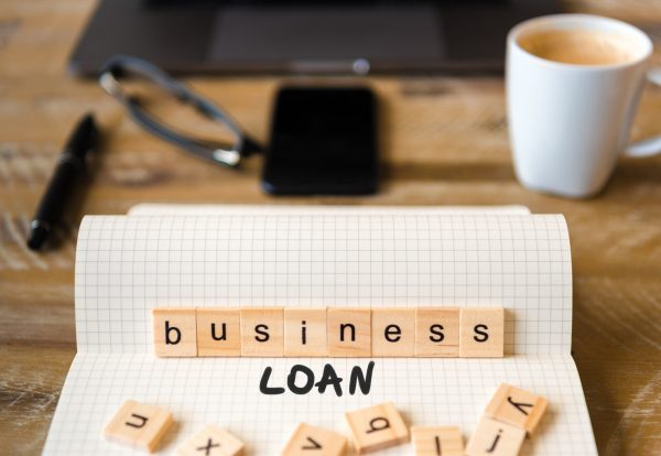 Closeup on notebook over vintage desk surface, front focus on wooden blocks with letters making Business Loan text. Business concept image with office tools and coffee cup in background