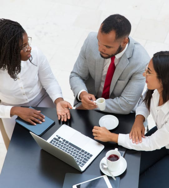 Diverse business team drinking coffee and discussing new ideas. Business man and women sitting at table with laptop and cups and talking. Corporate meeting concept.