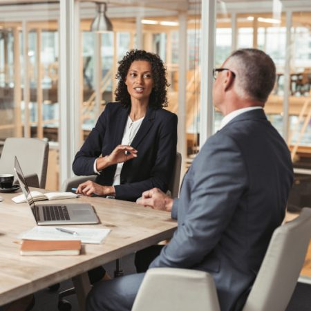 65787964 - mature businessman and young work colleague discussing business while sitting together at a table in an office boardroom